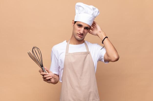 Jonge bakkersman die zich gestrest, bezorgd, angstig of bang voelt, met de handen op het hoofd, in paniek raakt bij vergissing