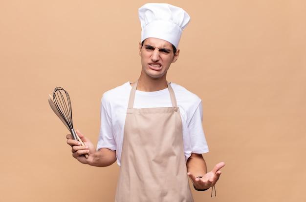 Jonge bakkersman kijkt boos, geïrriteerd en gefrustreerd schreeuwend wtf of wat is er mis met je