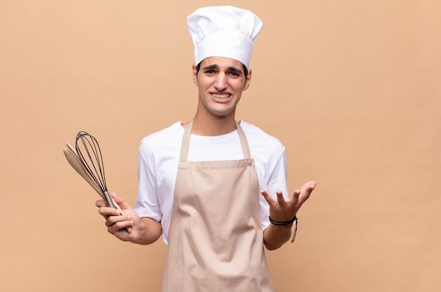 Jonge bakkersman kijkt wanhopig en gefrustreerd, gestrest, ongelukkig en geïrriteerd, schreeuwend en schreeuwend