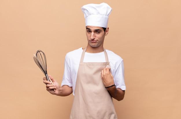 Jonge bakkersmens die arrogant, succesvol, positief en trots kijkt, wijzend naar zichzelf