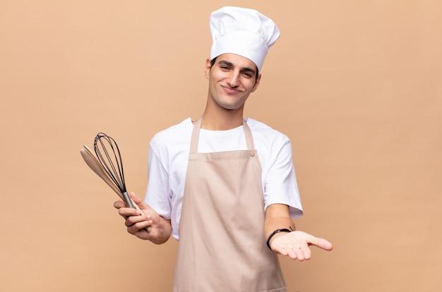 Jonge bakkersmens die gelukkig glimlacht met vriendelijke, zelfverzekerde, positieve blik, een object of concept aanbiedt en toont