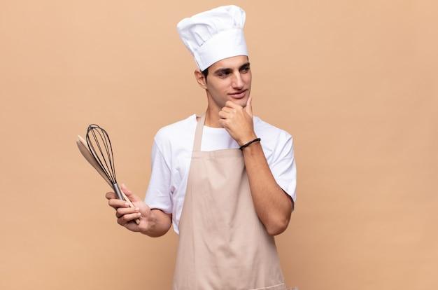 Jonge bakkersmens die met een gelukkige, zelfverzekerde uitdrukking met hand op kin glimlacht, zich afvraagt en naar de kant kijkt