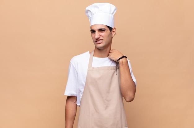 Jonge bakkersmens die zich gestrest, angstig, moe en gefrustreerd voelt, de hals van het shirt trekt, gefrustreerd kijkt door het probleem