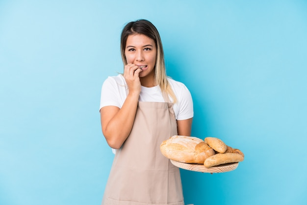 Jonge bakkersvrouw bijtende nagels, nerveus en erg angstig