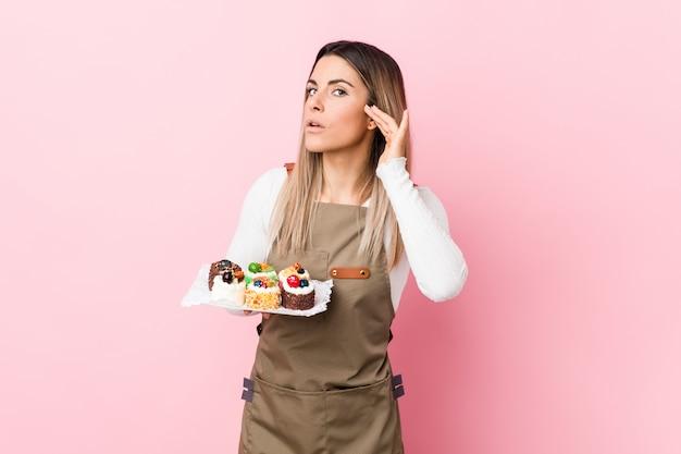 Jonge bakkersvrouw die snoepjes houden die aan het luisteren van een roddel proberen.