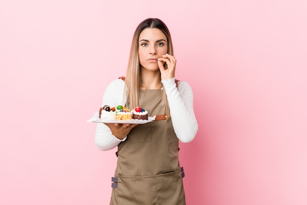 Jonge bakkersvrouw die snoepjes met vingers op lippen houdt die een geheim houden