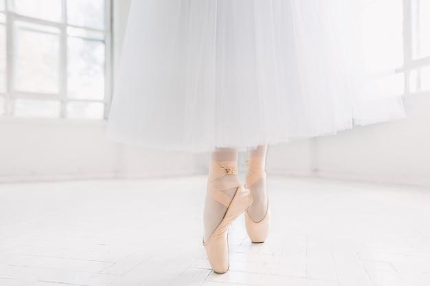 Jonge ballerina, close-up op benen en schoenen, staande in pointe-positie.