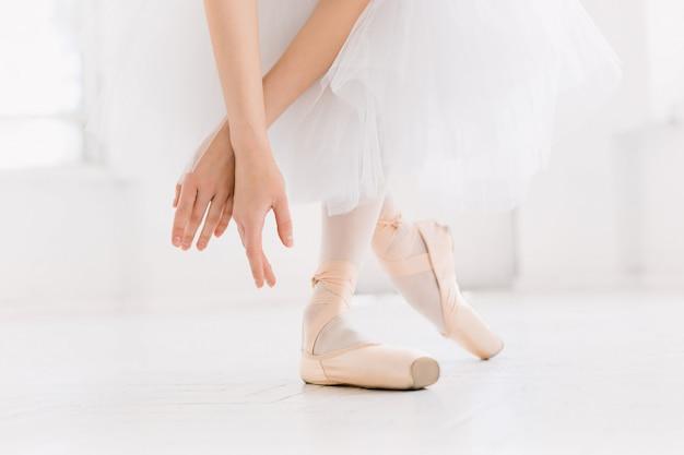 Jonge ballerina dansen, close-up op benen en schoenen, staande in spitse positie.
