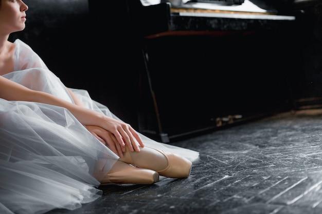 Jonge ballerina dansen, close-up op benen en schoenen, zittend in pointe shooses