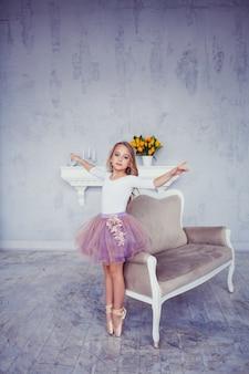 Jonge ballerina danser in roze jurk