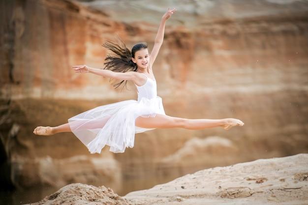 Jonge ballerina in een witte jurk in een sprong