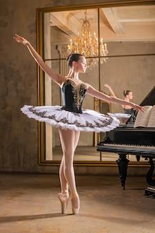 Jonge ballerina in een witte tutu dansen op een mooie oude piano in een vintage interieur