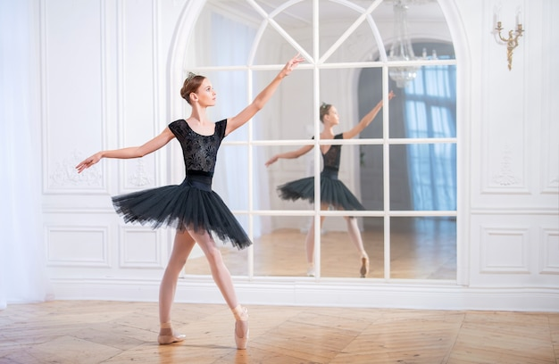 Jonge ballerina in een zwarte tutu staat in een sierlijke pose op pointe-schoenen in een grote lichte zaal voor een spiegel.