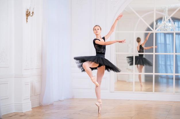 Jonge ballerina in een zwarte tutu staat op spitzen in een elegante pose in een grote, lichte zaal voor een spiegel.