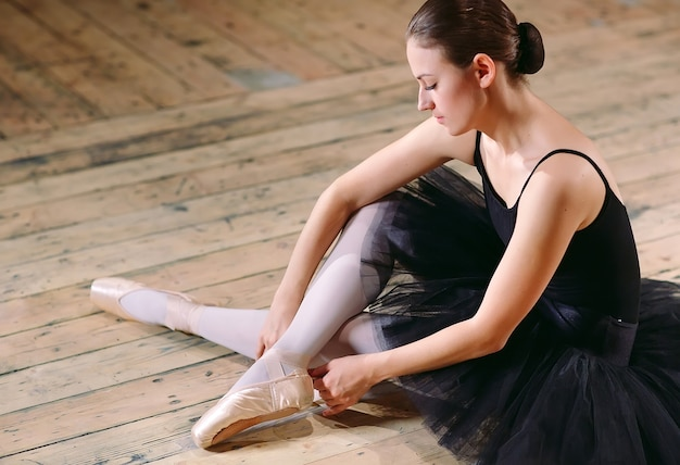 Jonge ballerina in zwarte jurk traint achter de schermen.