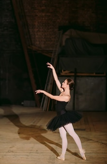 Jonge ballerina in zwarte jurk treinen achter de schermen.