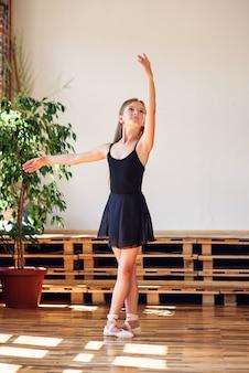 Jonge ballerina in zwarte tutu die dansbewegingen uitoefent.
