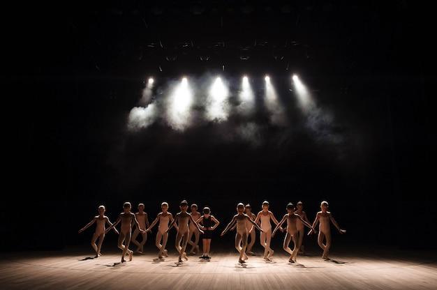 Jonge ballerina's repeteren in de balletles. ze voeren verschillende choreografische oefeningen uit en staan in verschillende houdingen.