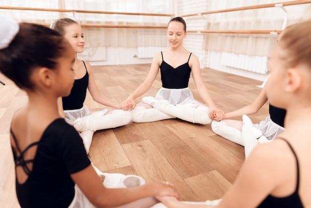 Jonge ballerina's voeren verschillende choreografische oefeningen uit.