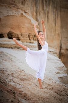 Jonge ballerina staat in een sierlijke pose aan de rand van een zanderige klif