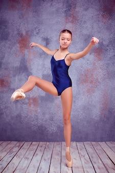 Jonge ballerinadanser die haar technieken op lila achtergrond van muur en houten vloer toont