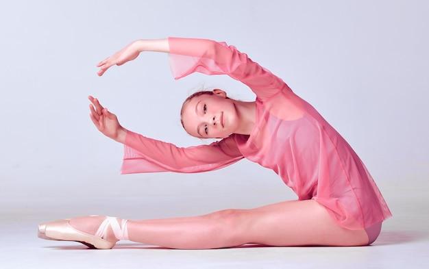 Jonge ballerinadanseres in roze jurk die haar technieken toont op lila achtergrond
