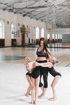 Jonge ballerinameisjes die zich rond de vrouwelijke leraar in dansklasse bevinden