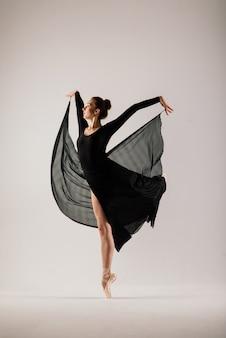 Jonge ballet danseres geïsoleerd op een witte muur