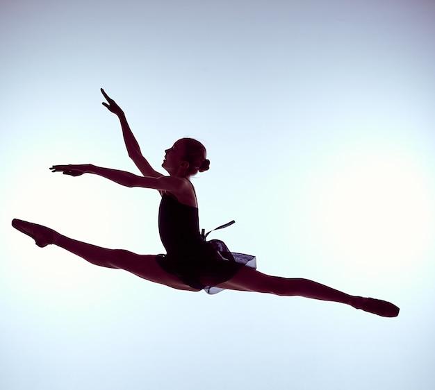 Jonge balletdanser die op een grijze achtergrond springt ballerina draagt in blauwe jurk