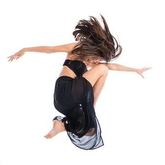 Jonge balletdanser die over witte achtergrond springt