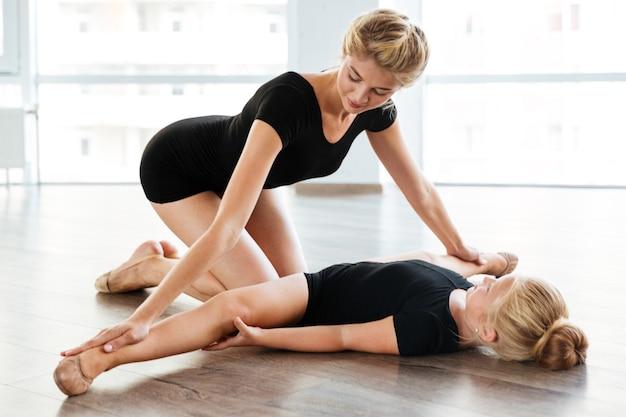 Jonge balletleraar en haar kleine student in balletles
