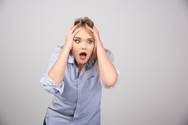 Jonge bang blonde vrouw met geopende mond hand in hand op het hoofd.