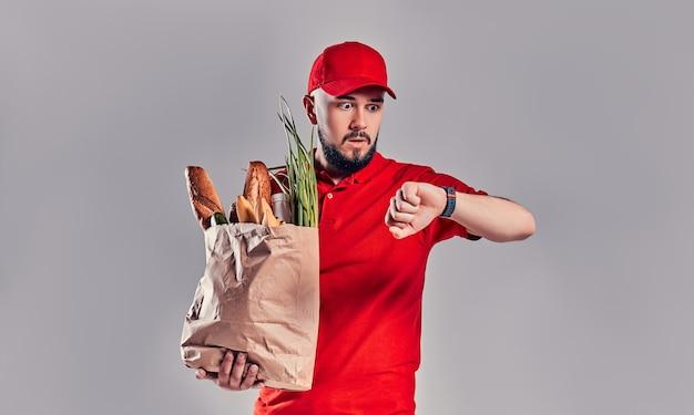 Jonge, bange, bebaarde bezorger in rood uniform houdt een pakket met brood en groenten vast en kijkt naar een smartwatch die laat is geïsoleerd op een grijze achtergrond.