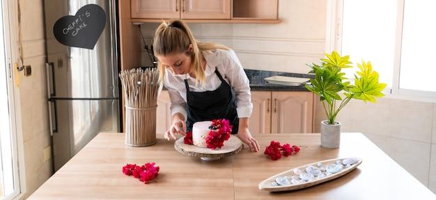 Jonge banketbakker die een traditionele roodfluwelen cake kookt in de keuken