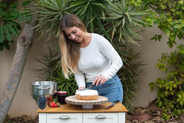Jonge banketbakker die een zoete cake in de keuken kookt