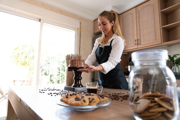Jonge banketbakker kookt een heerlijke zelfgemaakte chocoladetaart met fruit in de keuken