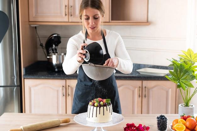 Jonge banketbakker kookt een heerlijke zelfgemaakte witte chocoladetaart met fruit in de keuken