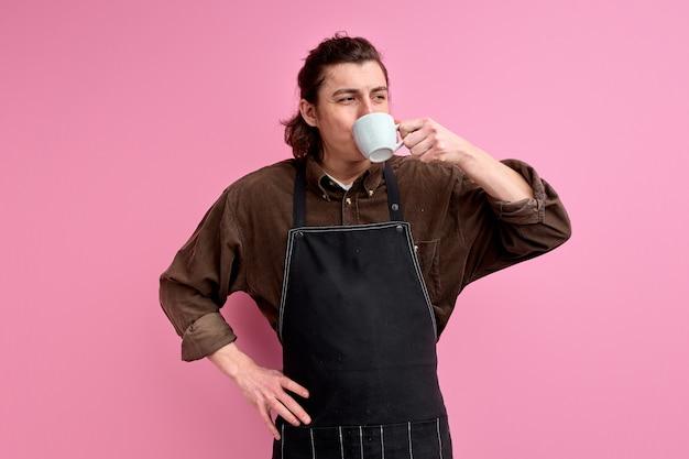 Jonge barista die van koffie in mok geniet, die zwarte schort draagt. knappe blanke man staan drank drinken