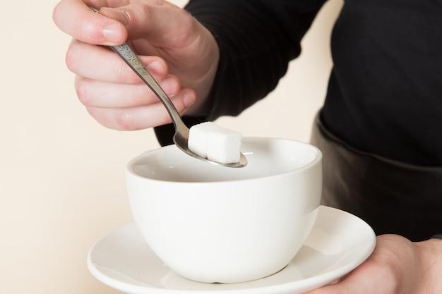 Jonge barista in zwart pak met ingrediënten en koffie-apparatuur bruine koffie zaden op wit