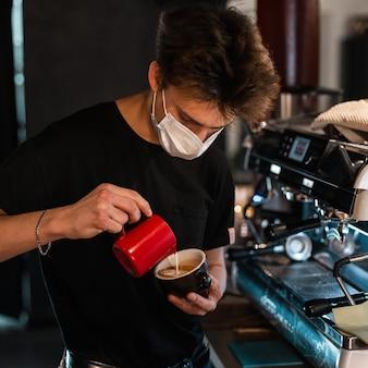 Jonge barista-man met een medisch masker in een zwart t-shirt maakt heerlijke koffie in de buurt van een koffiezetapparaat in een café. coronavirus-concept