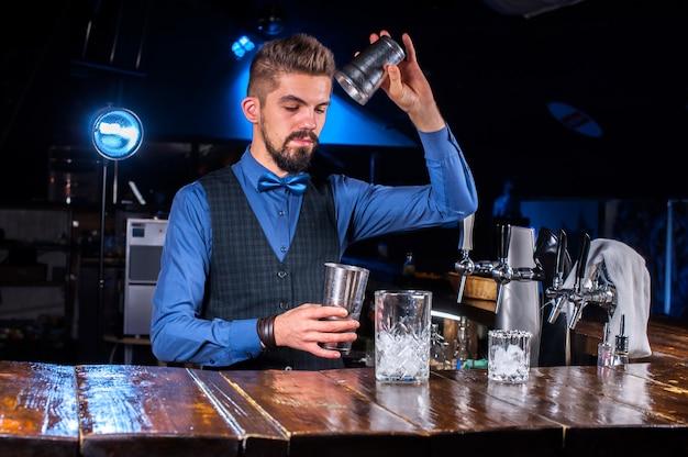 Jonge barkeeper demonstreert het proces van het maken van een cocktail terwijl hij naast de bar in de nachtclub staat