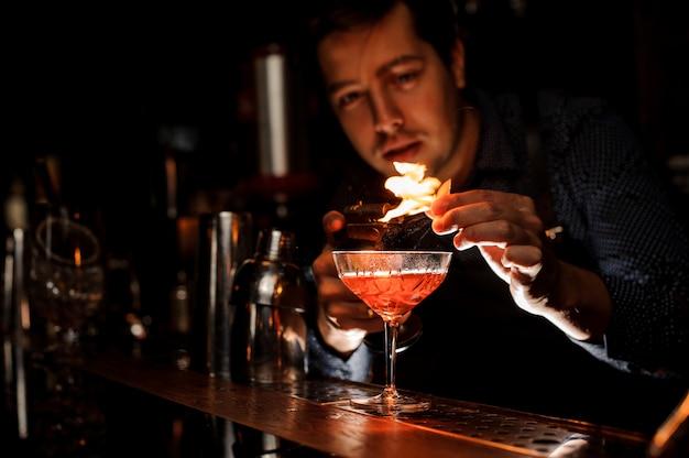 Jonge barman die een verse cocktail met een rokerige nota maakt