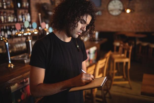 Jonge barman die op dagboek schrijft
