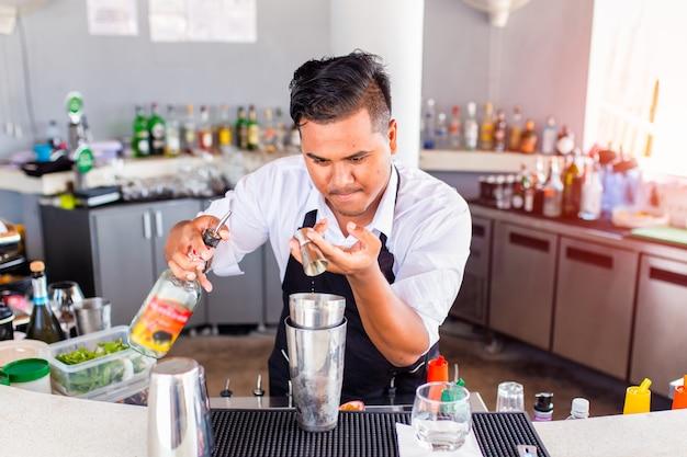 Jonge barman gieten cocktail in een bar, phuket, thailand