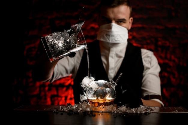 Jonge barman in masker met zwarte handschoenen giet drankje in speciale kolf