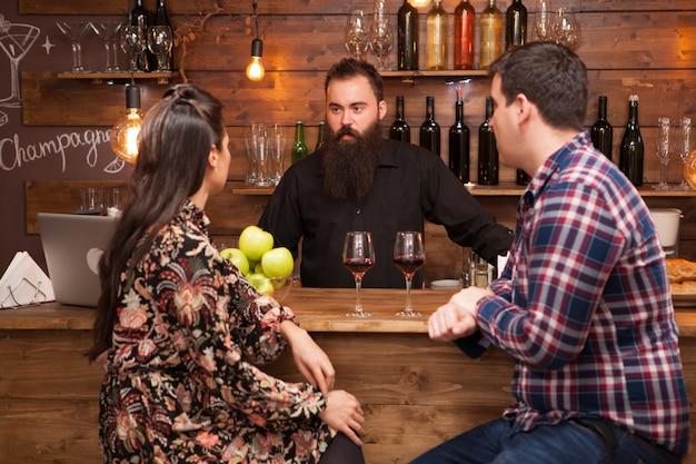 Jonge barman staat aan de toog en praat met een meisje en haar vriendje. hippe kroeg.