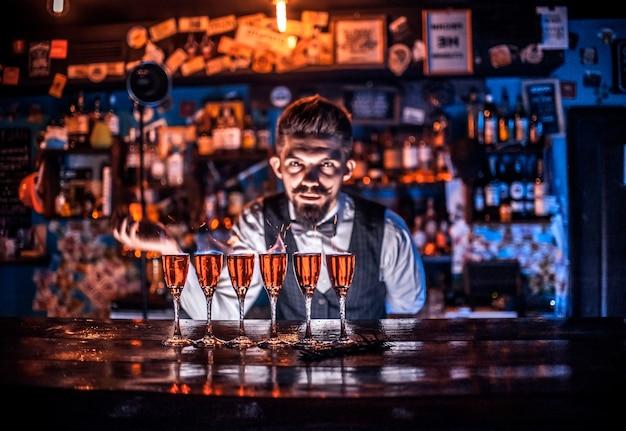Jonge bartending legt de laatste hand aan een drankje in de nachtclub