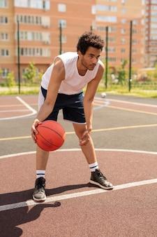 Jonge basketballer in activewear die voorover buigt tijdens het voorbereiden van het gooien van de bal tijdens het spelen