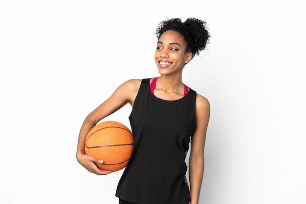 Jonge basketbalspeler latijnse vrouw geïsoleerd op een witte achtergrond op zoek naar de kant en lachend