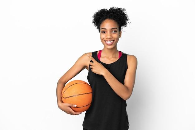 Jonge basketbalspeler latijnse vrouw geïsoleerd op een witte achtergrond wijzend naar de zijkant om een product te presenteren